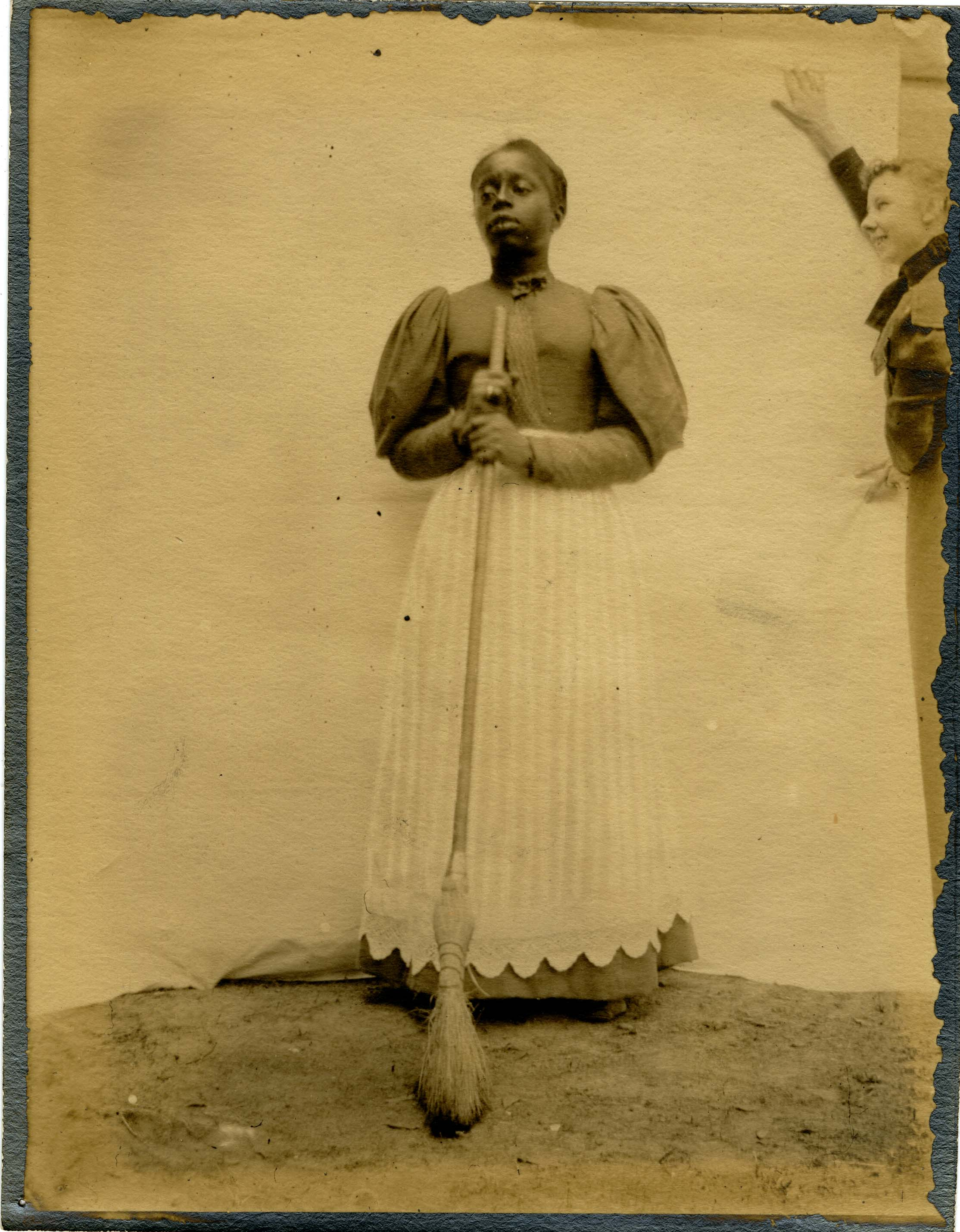 African American woman holds broom while white woman stands aside.
