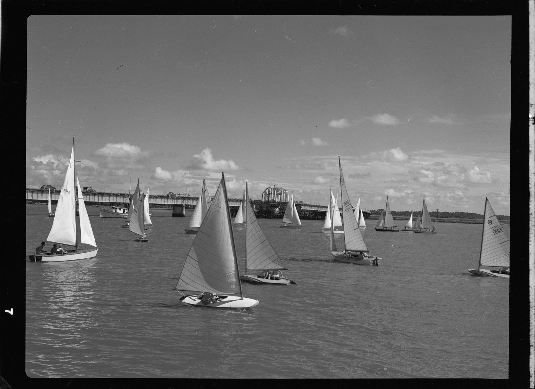 Sail boat races silhouetted by the open Lady's Island swing bridge