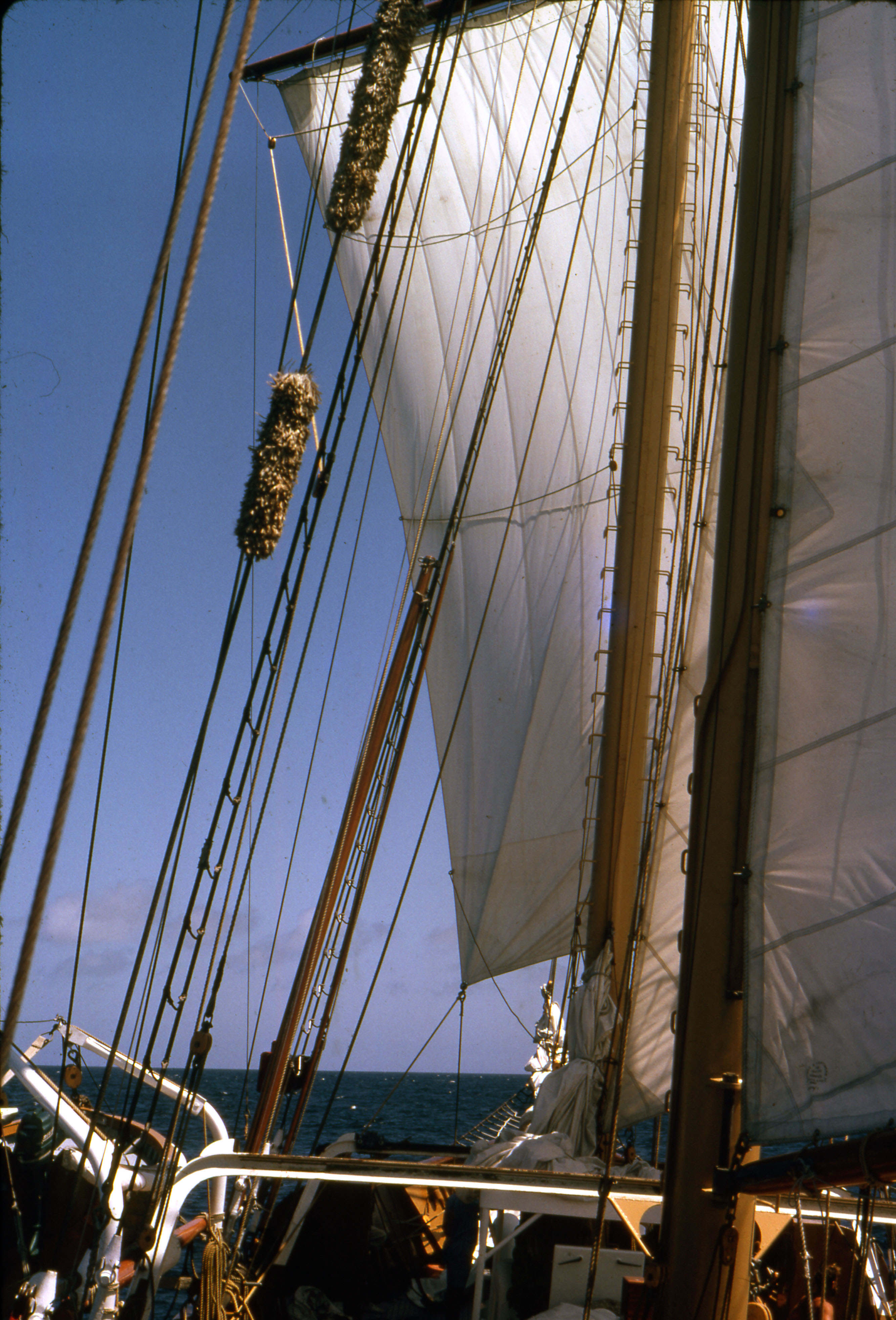 The mast and sails of a ship in the ocean around the Galapagos Islands.
