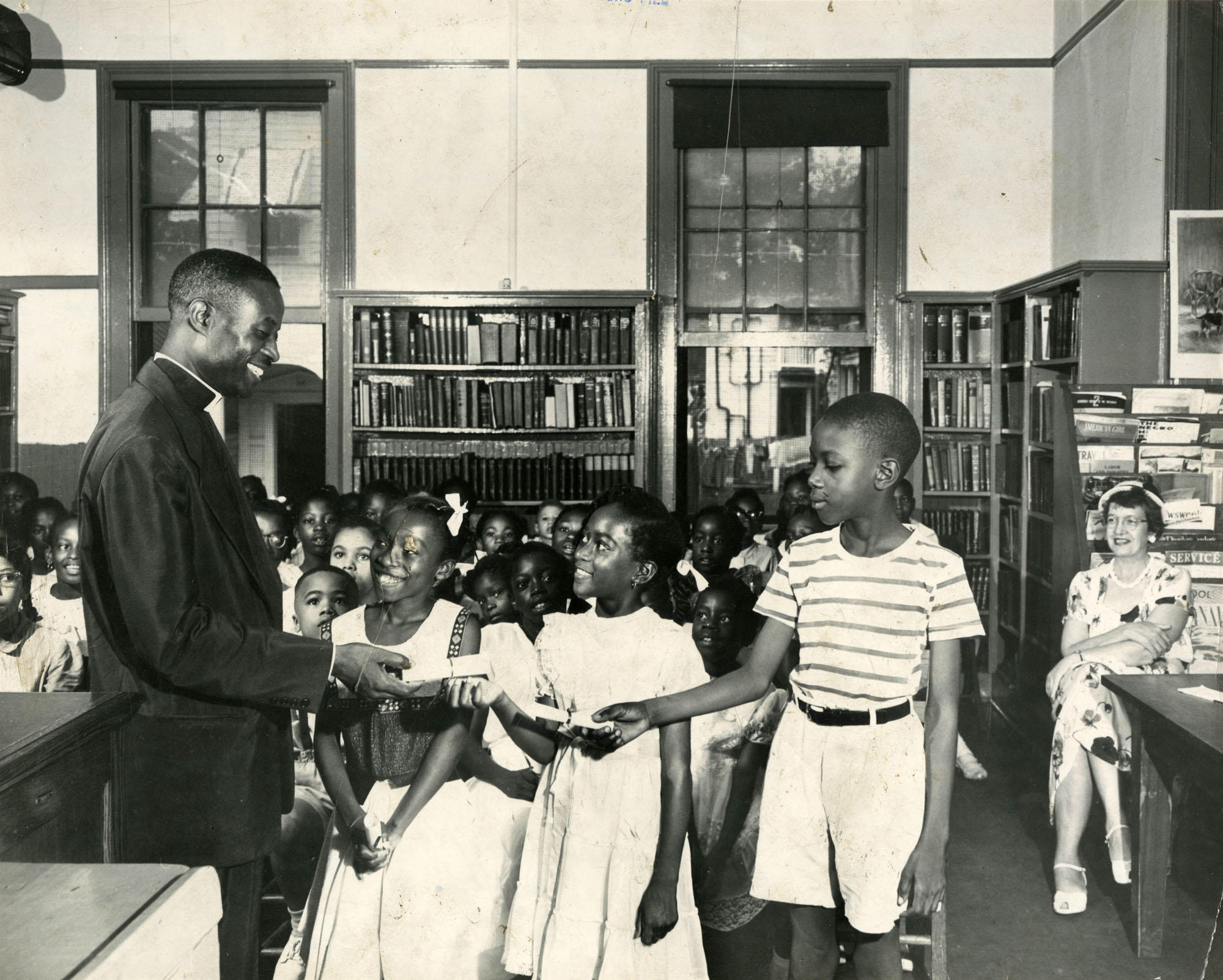 An African American man hands awards to three children during summer reading closing exercises at the Dart Hall Branch Library, Charleston SC 1953