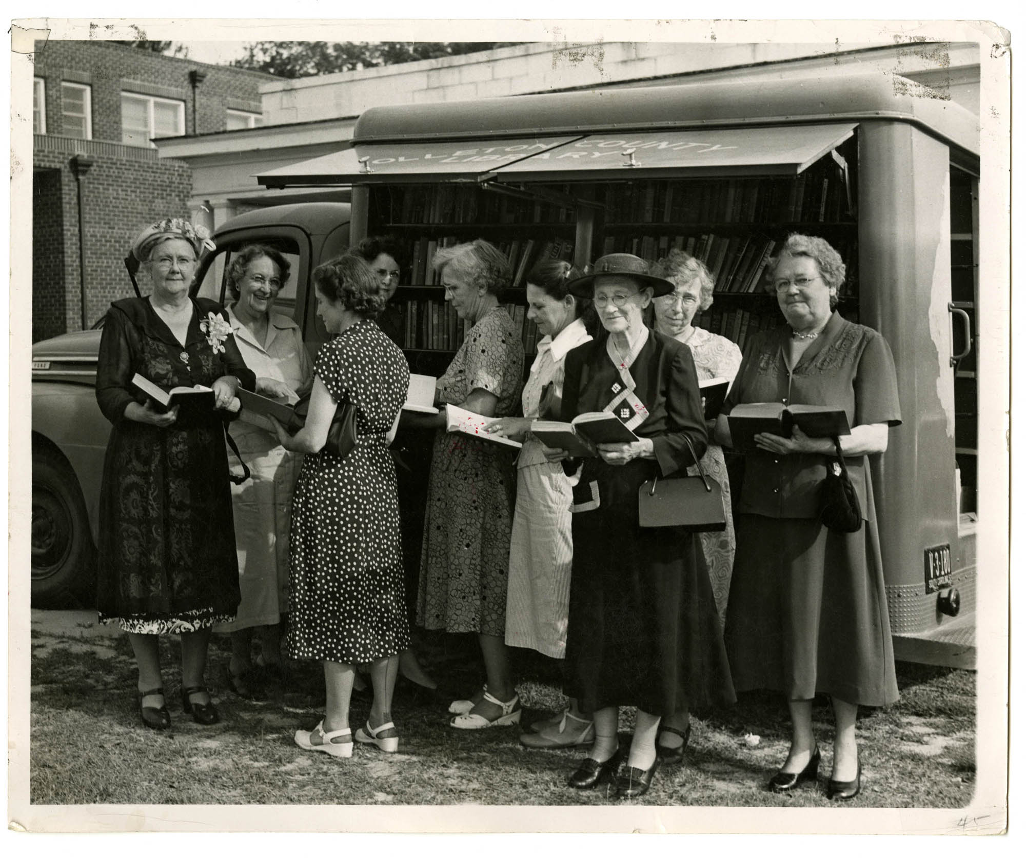 A group of women hold books beside bookmobile at Colleton County Library, 1952.