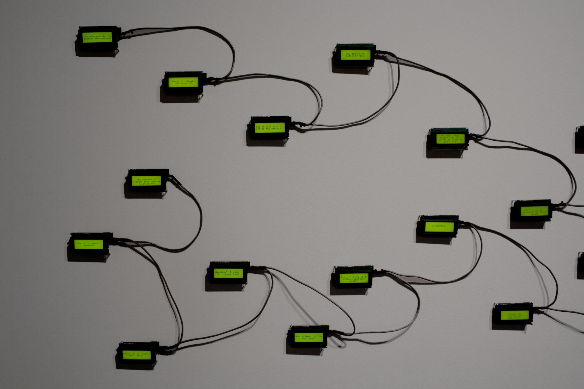A photograph of an installation by Rafael Lozano-Hemmer that includes several tiny green screens that are wired together. It appears there's different text on each of the screens.
