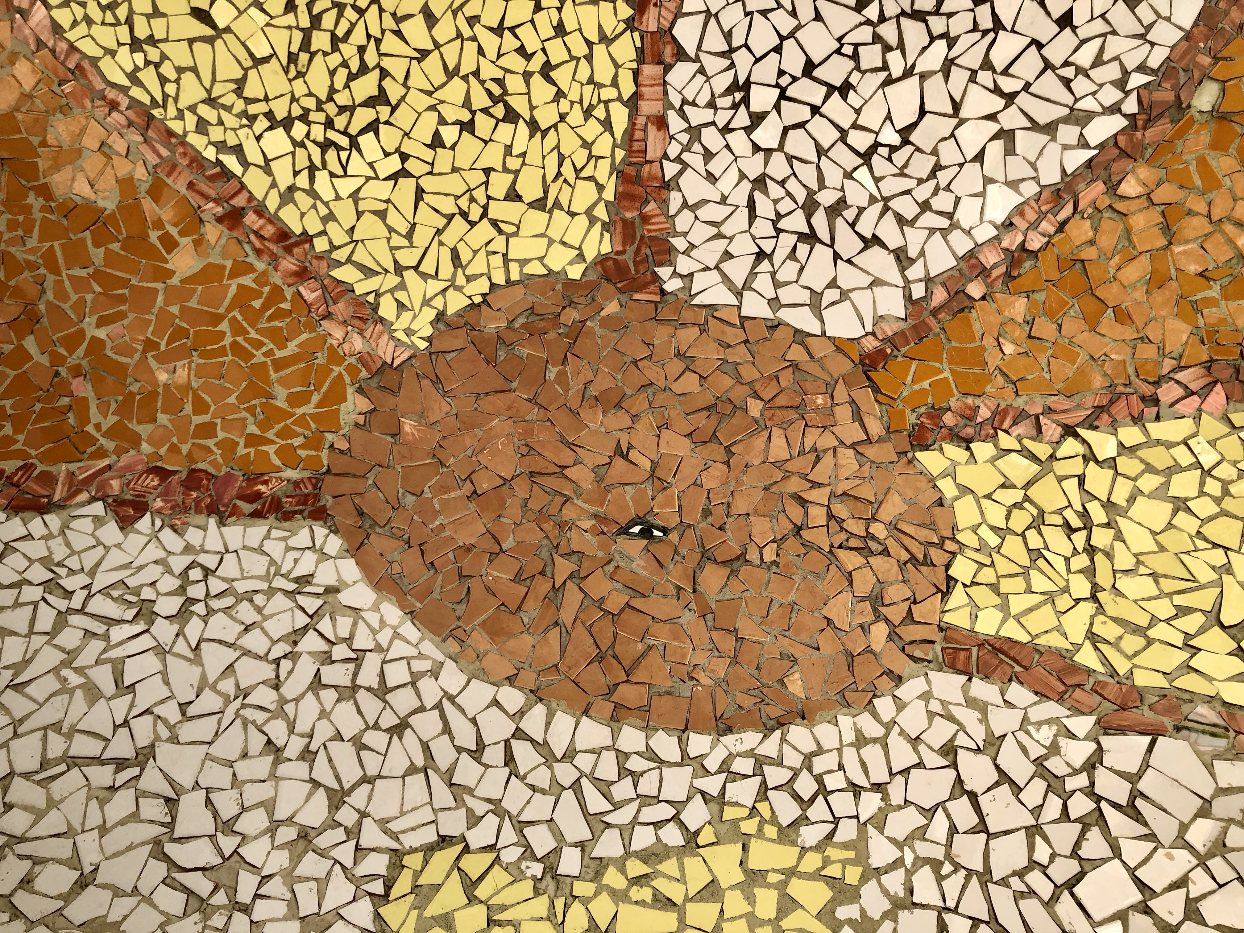 Photograph of a ceramic mosaic with beams of yellow, brown, and white coming from a brown circle with a black and white eyeball in the center.