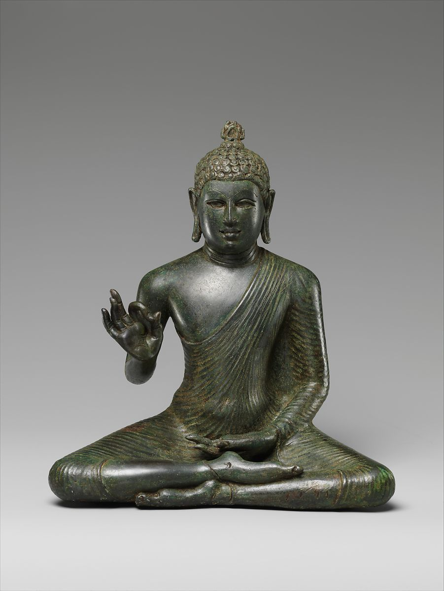 Sculpture of Buddha sitting with his legs folded, one hand in his lap and his other with his pointer finger and thumb touching.