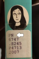 An image of a call number on a side of a book. An arrow points to the first line.