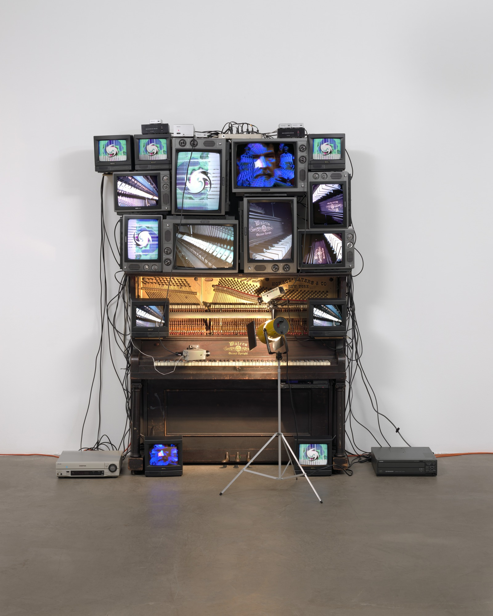 Photograph of an installation made of Player piano, fifteen televisions, two cameras, two laser disc players, one electric light and light bulb, and wires.
