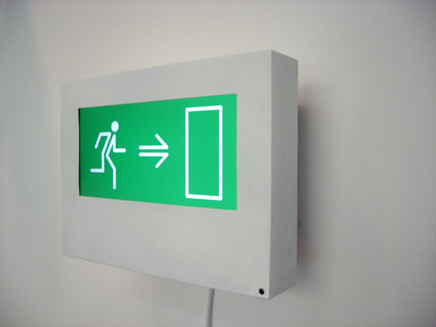 Installation piece by Freddie Yauner that looks like an exit sign. On the sign there is a person, an arrow, and a door.