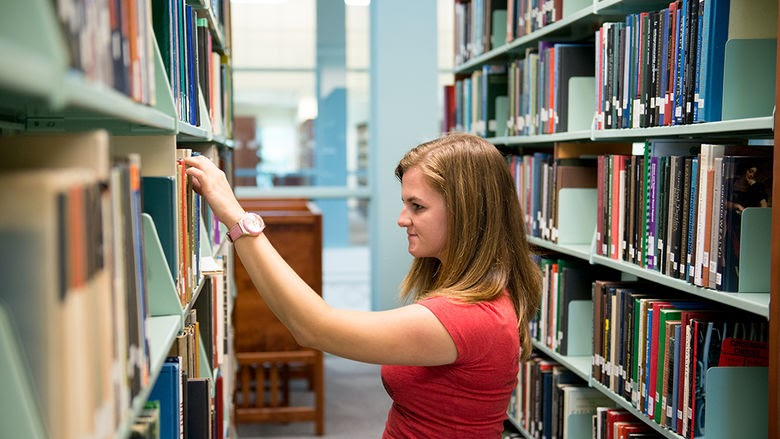 Woman browsing library shelves.
