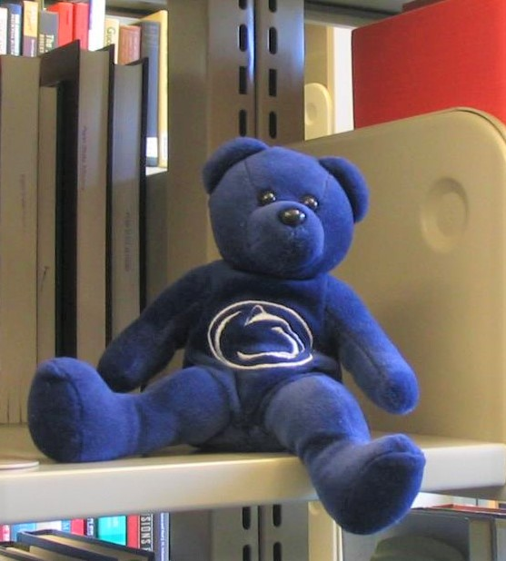Blue teddy bear with a Penn State logo on its chest, sitting on a library shelf
