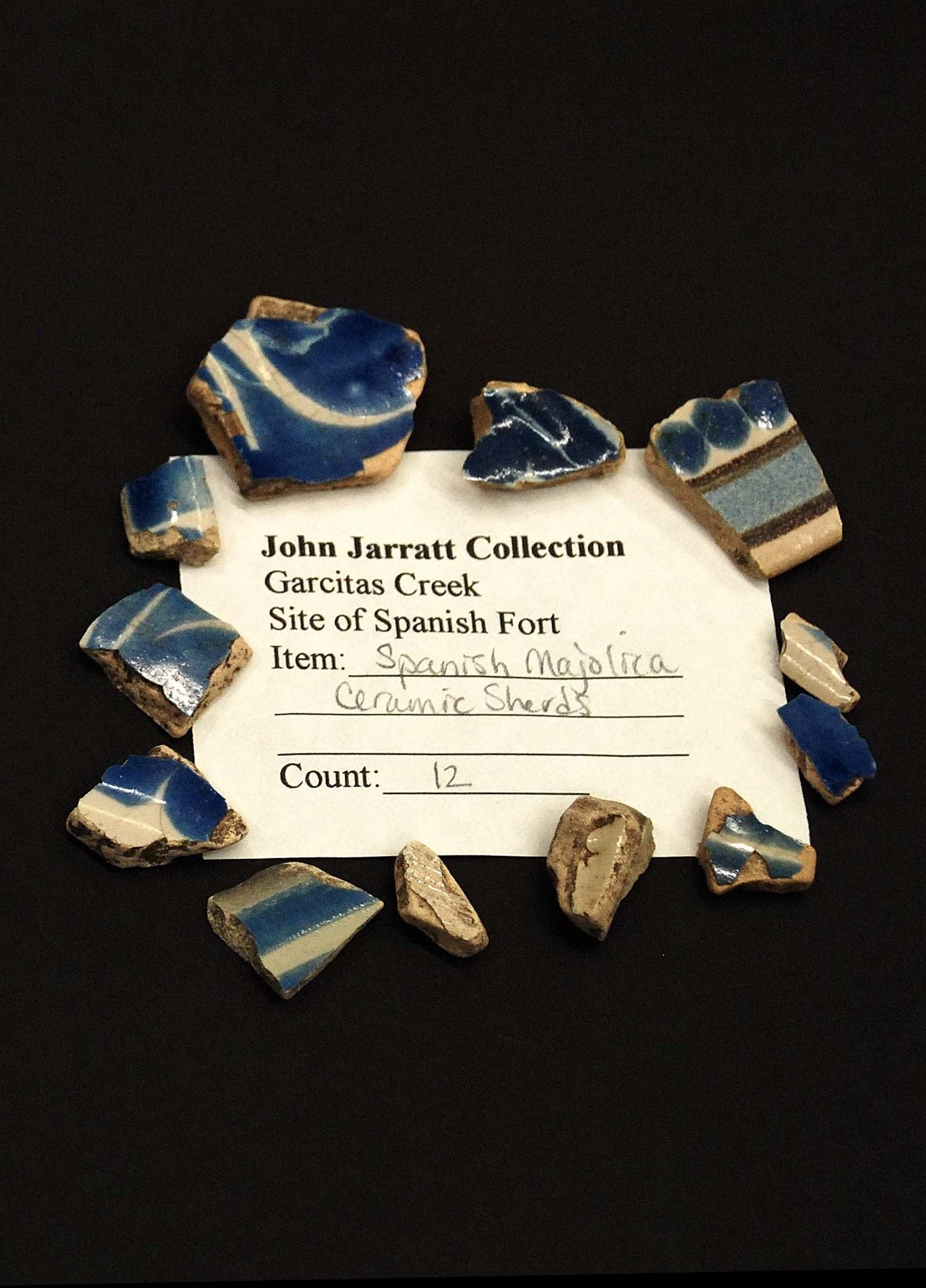 A label with the text John Jarratt Collection...Spanish Majolica Ceramic Shards surrounded by blue ceramic shards