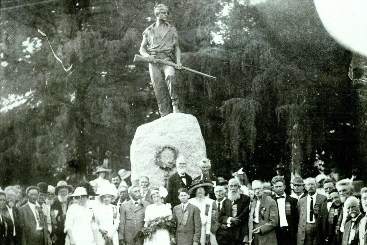 Black and white photo of the last stand monument with a crowd of people standing below it