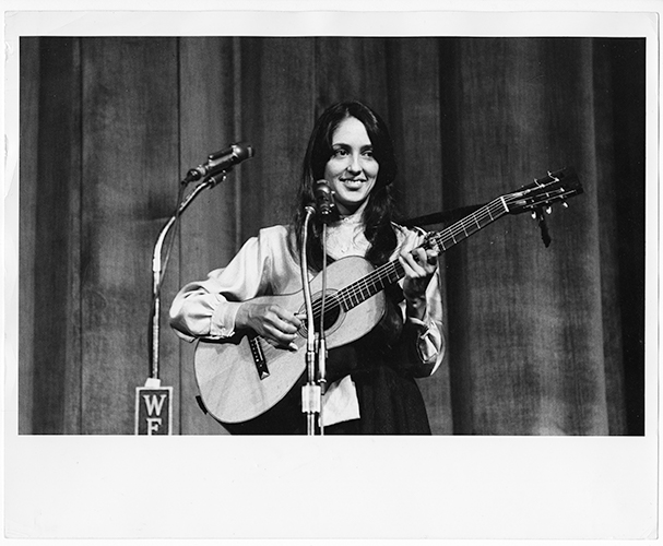 Joan Baez with guitar behind mic stand