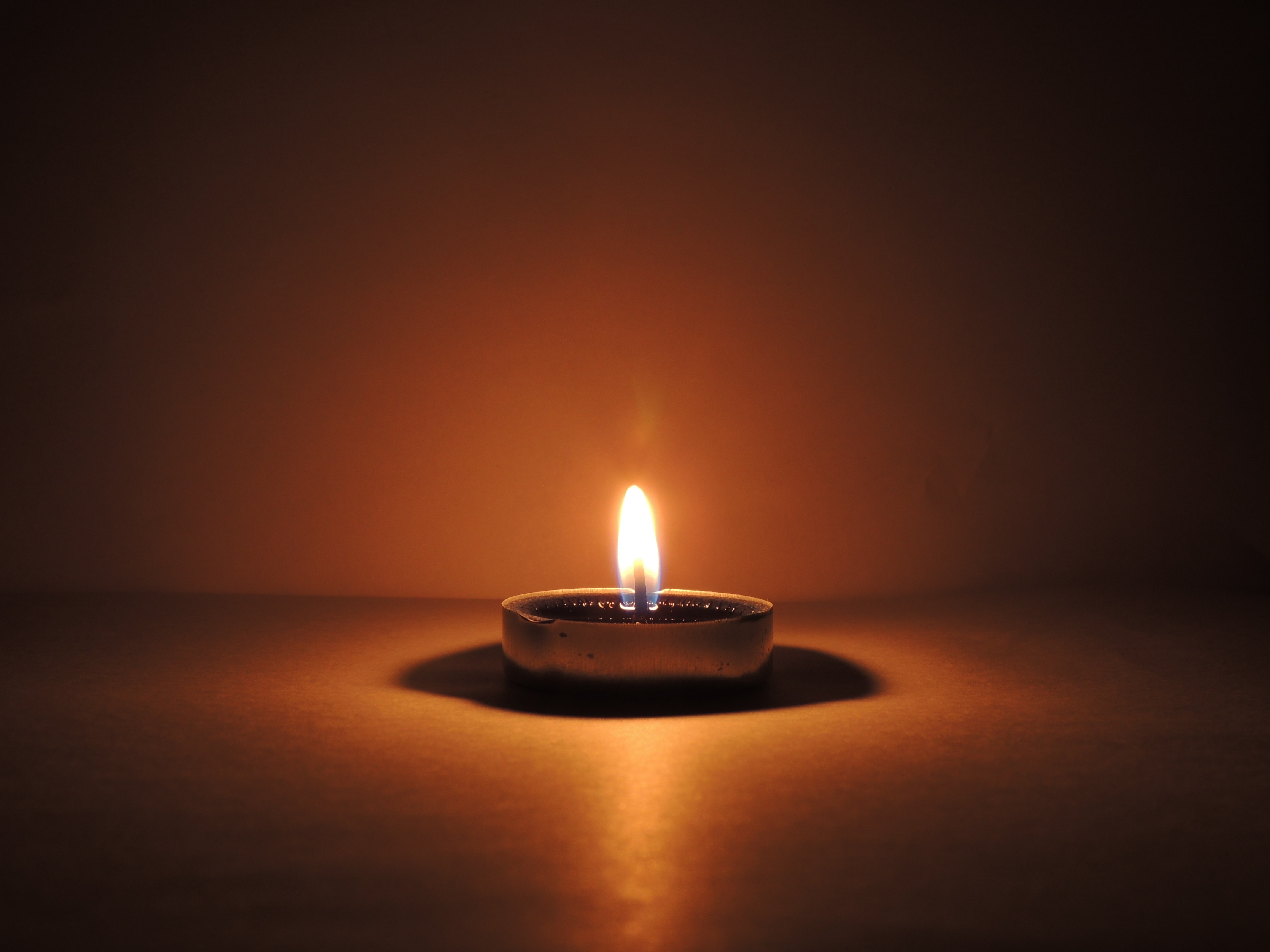 Image of a candle illuminating a dark room
