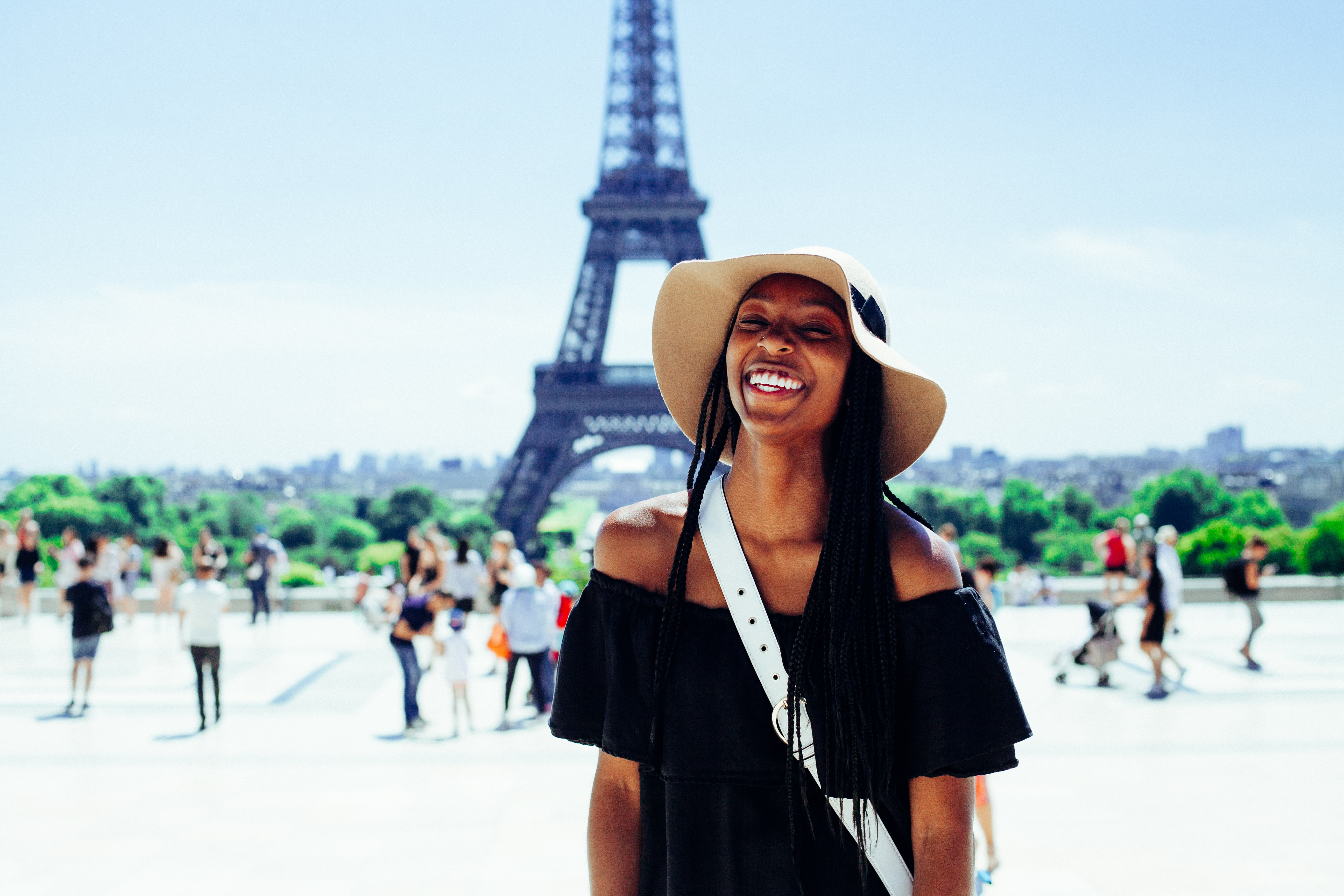 Girl smiling in front of the Eiffel Tower in Paris, France