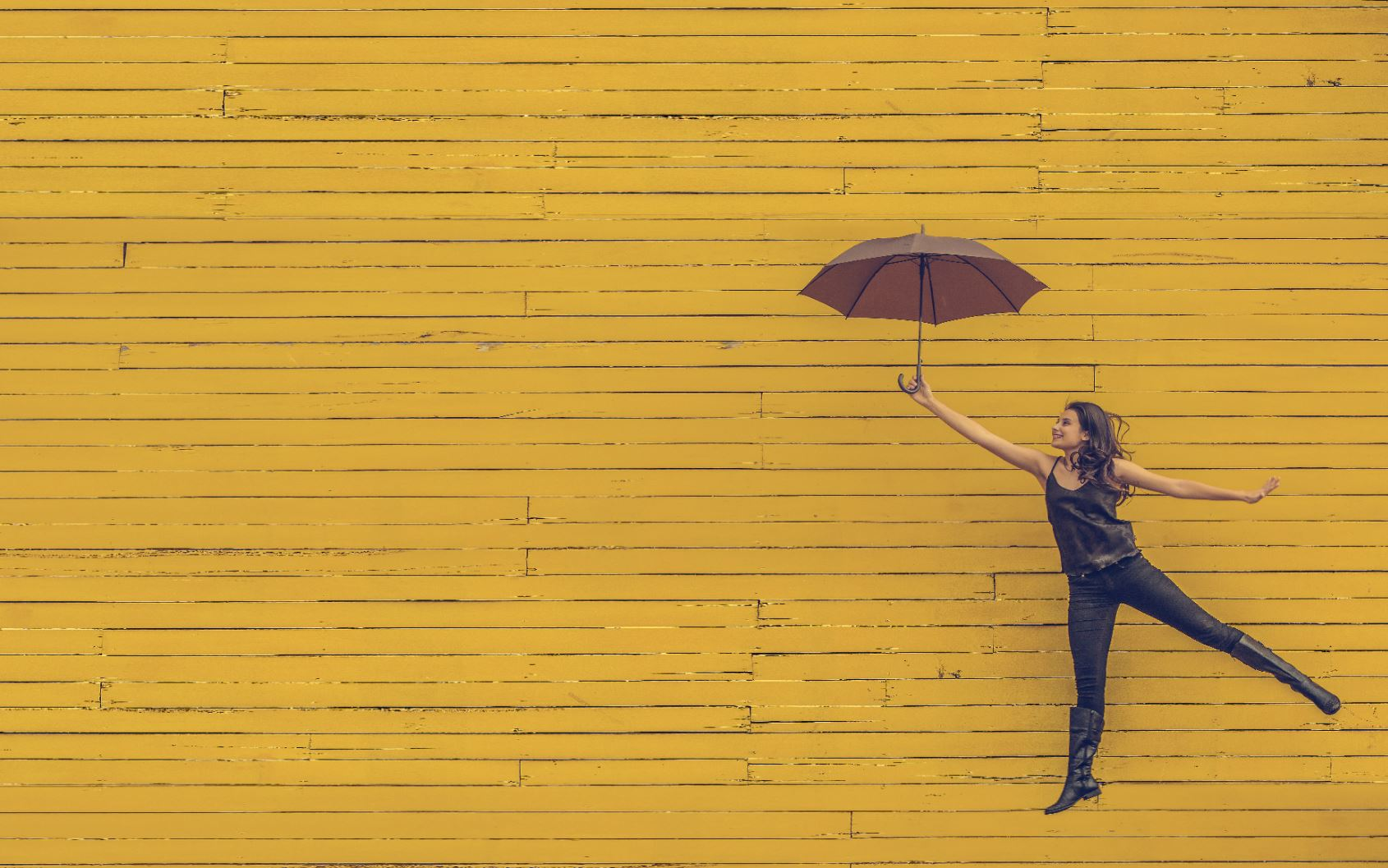 Girl smiling holding umbrella in front of bright yellow wall
