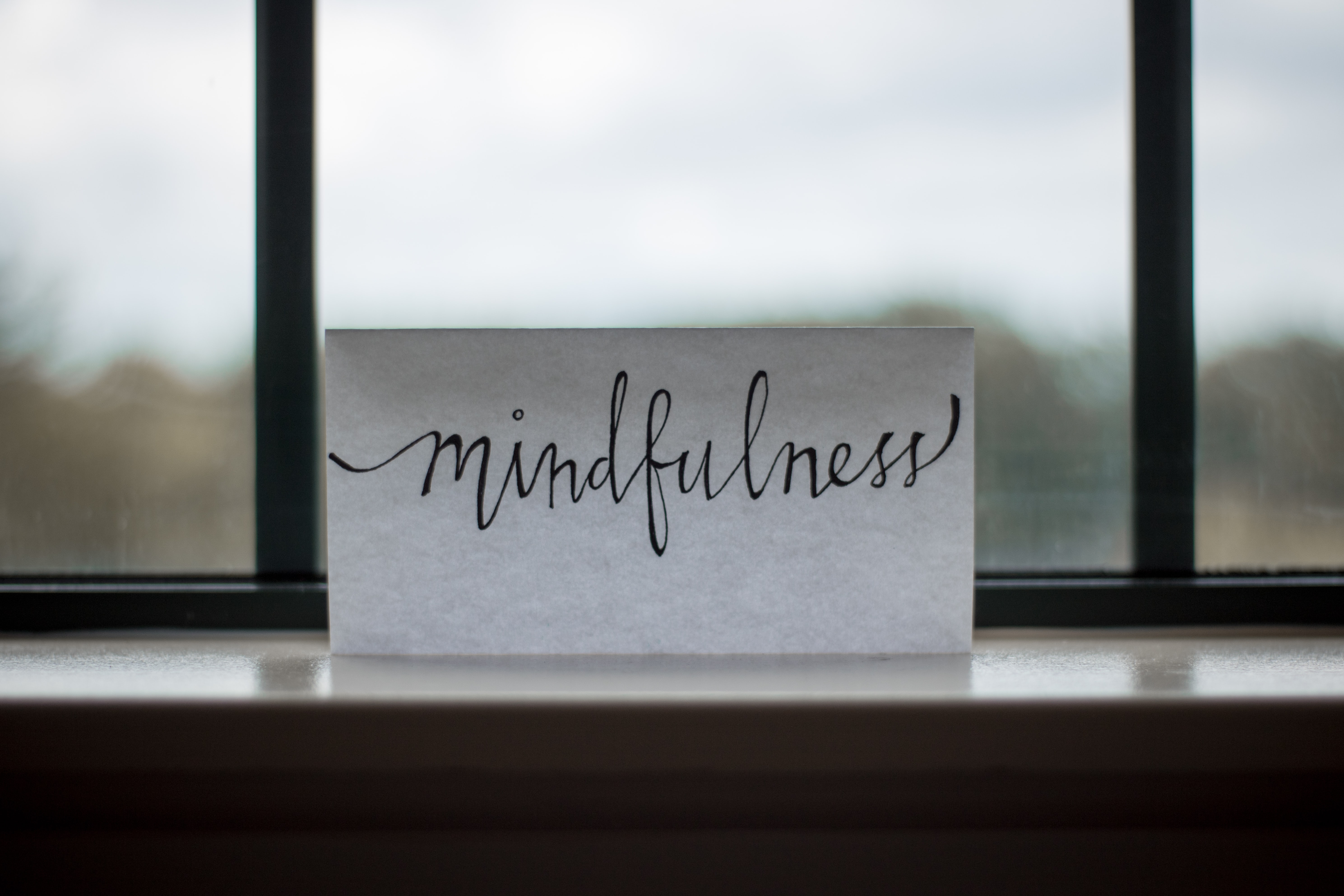 Piece of paper with the word mindfullness written in cursive on it