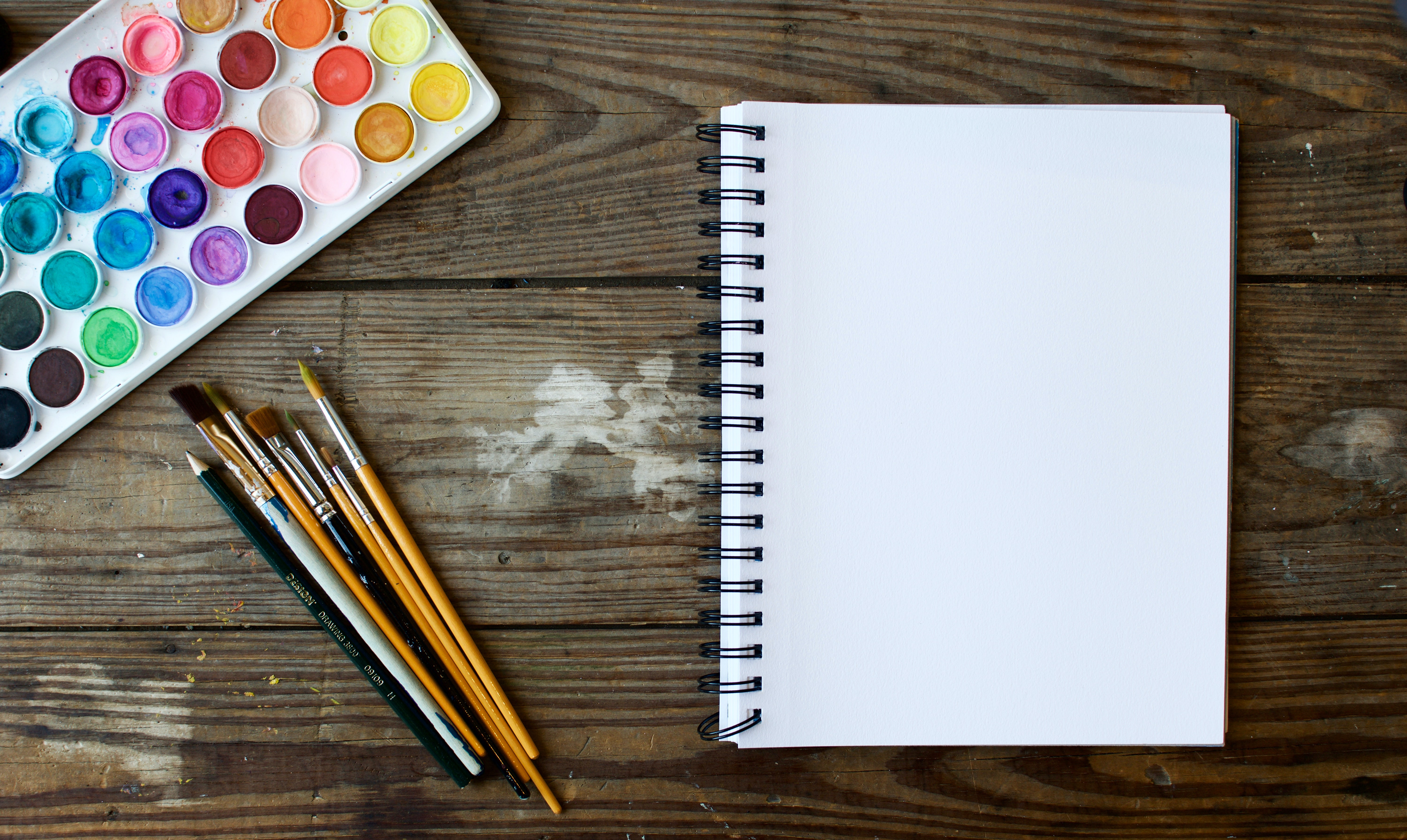 photo of watercolor paints and paintbrushes next to a blank notebook