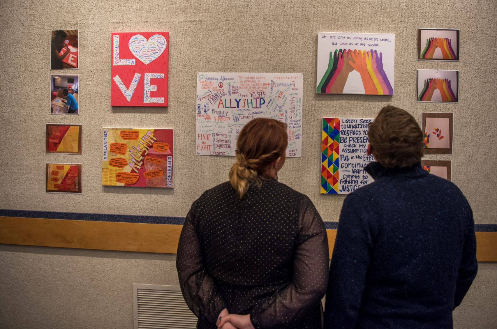 UConn students looking at student art show paintings about love and allyship