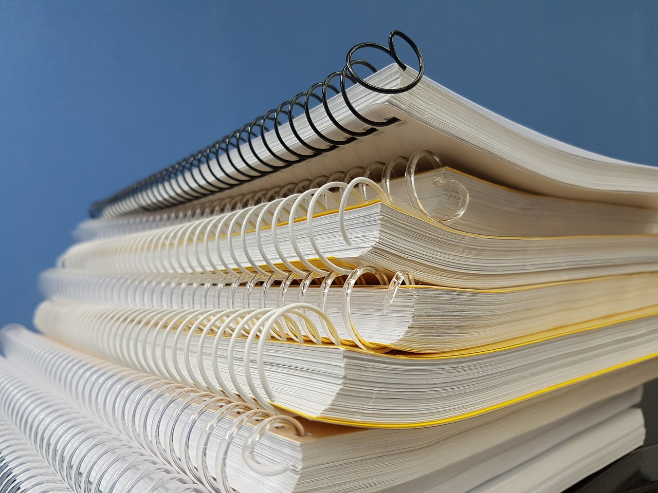 Image of several paper notebooks stacked up.
