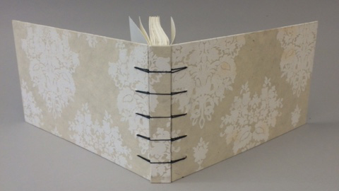 Hand sewn book with hard covers and exposed sewing on the spine