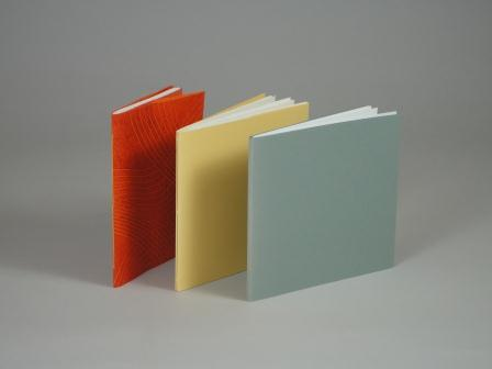 3 hand sewn pamphlets of different colors
