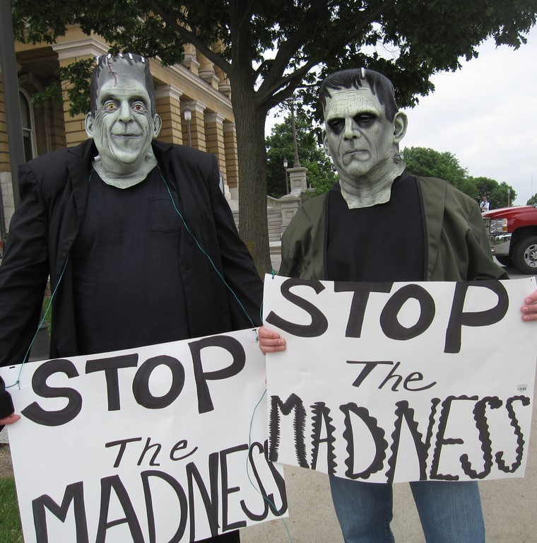 Two men wearing masks of Frankenstein's creature hold signs that say