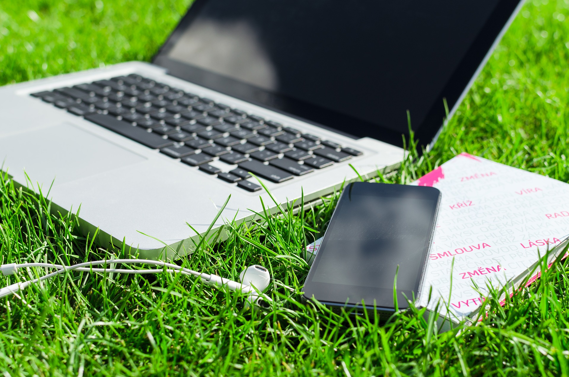 Laptop, phone, and notebook sitting on grass