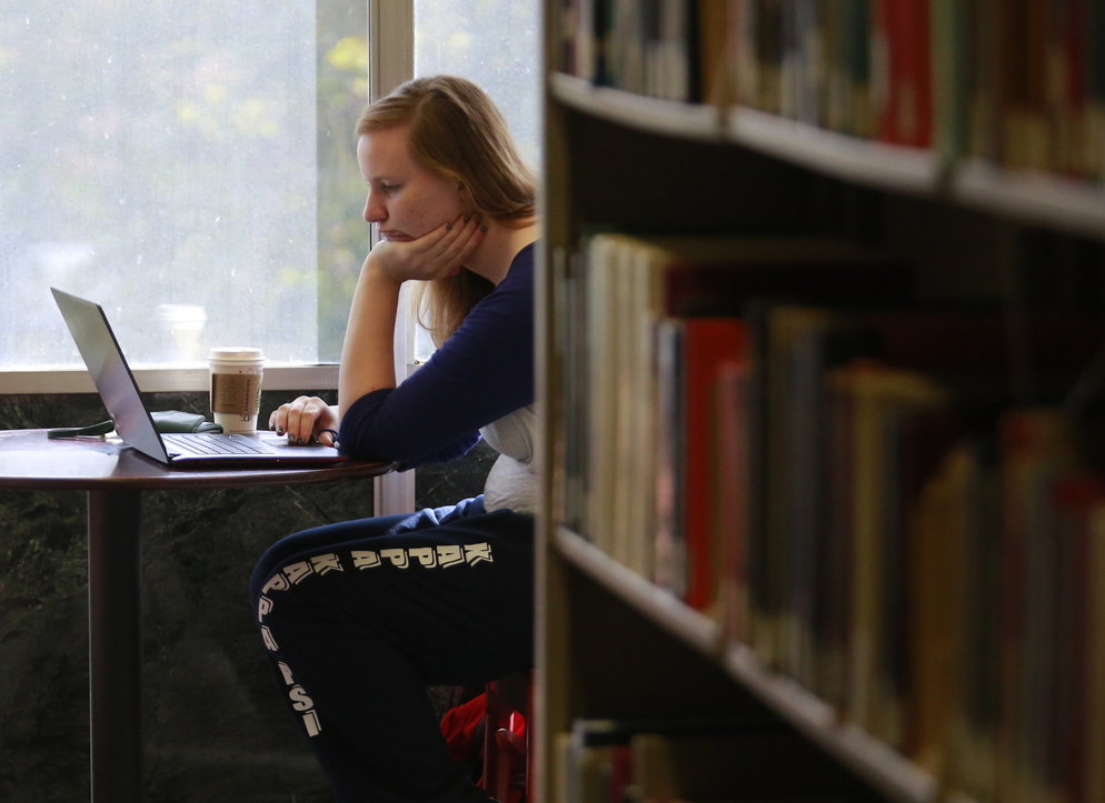Student studying next to shelf of books