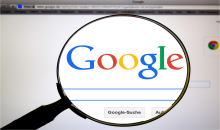the Google basic search screen magnified by a magnifying glass