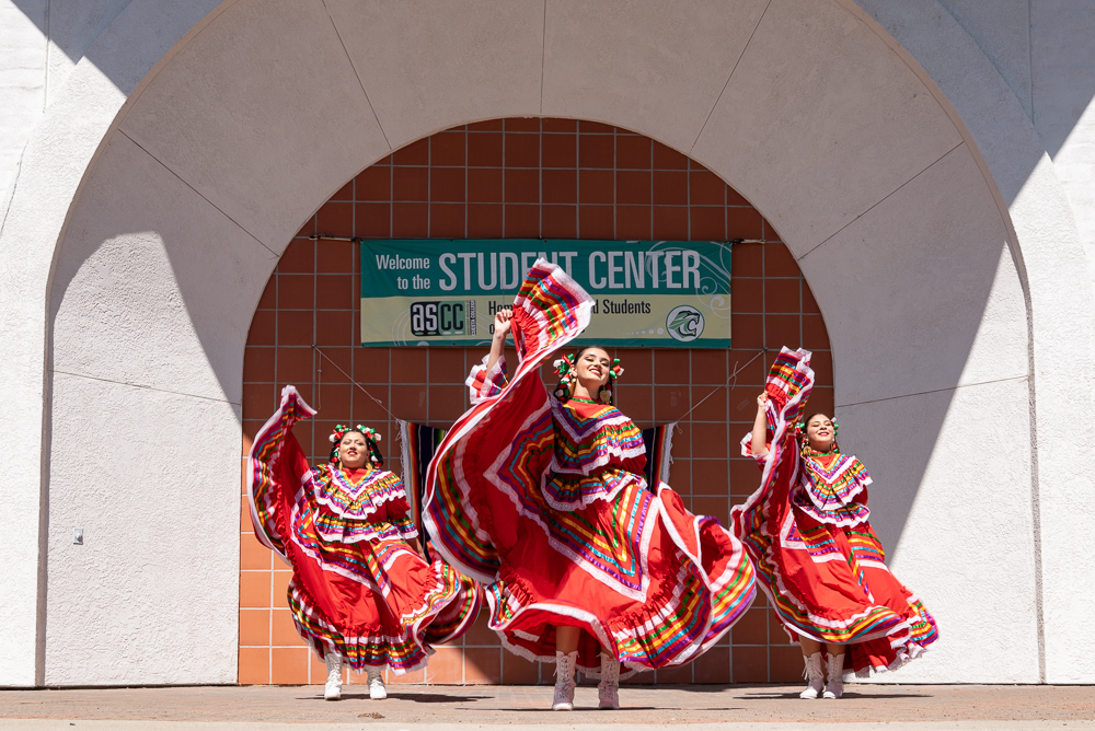 Three Mexican dancers perform in colorful dresses