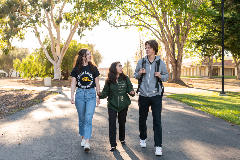 Three students are walking and talking together on the Cuesta College campus
