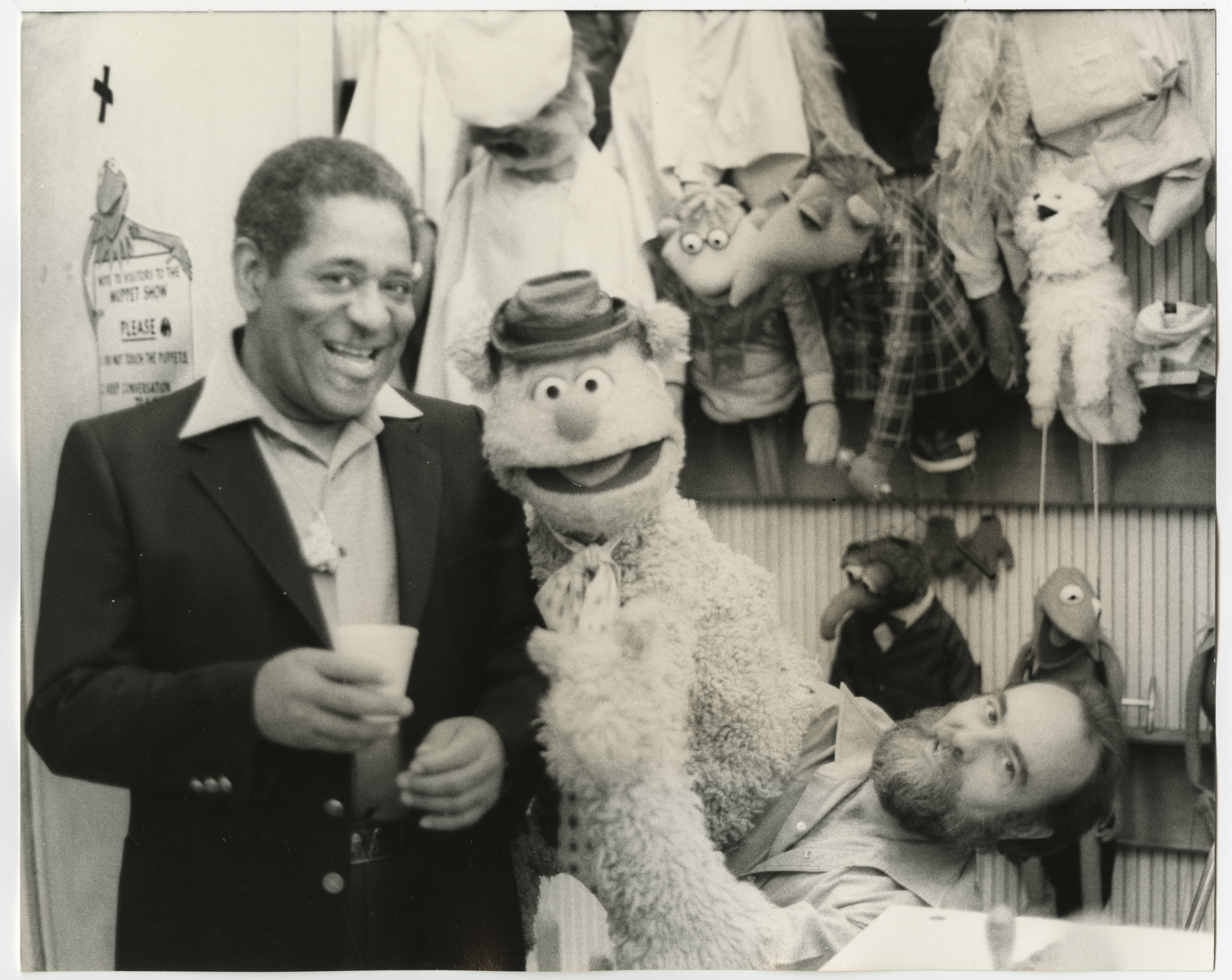 A black and white photograph of Dizzy Gillespie posing with Fozzie Bear and Jim Henson backstage at the Muppet Show. Henson is operating the puppet.