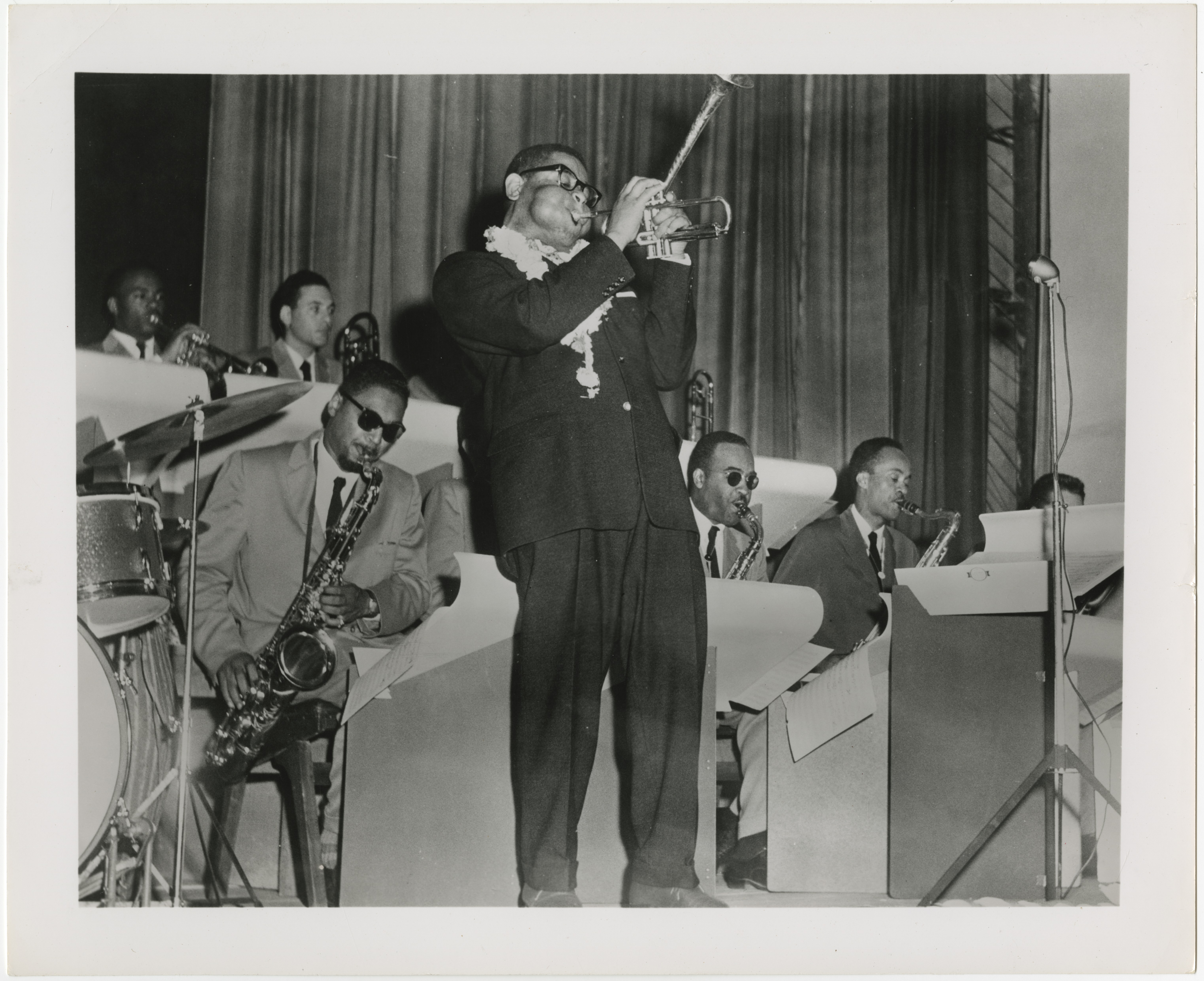 A black and white photograph of Dizzy Gillespie playing with his band. Dizzy is standing in front of a microphone playing trumpet with his characteristic blown out cheeks. Three saxophonists are seated directly behind him.