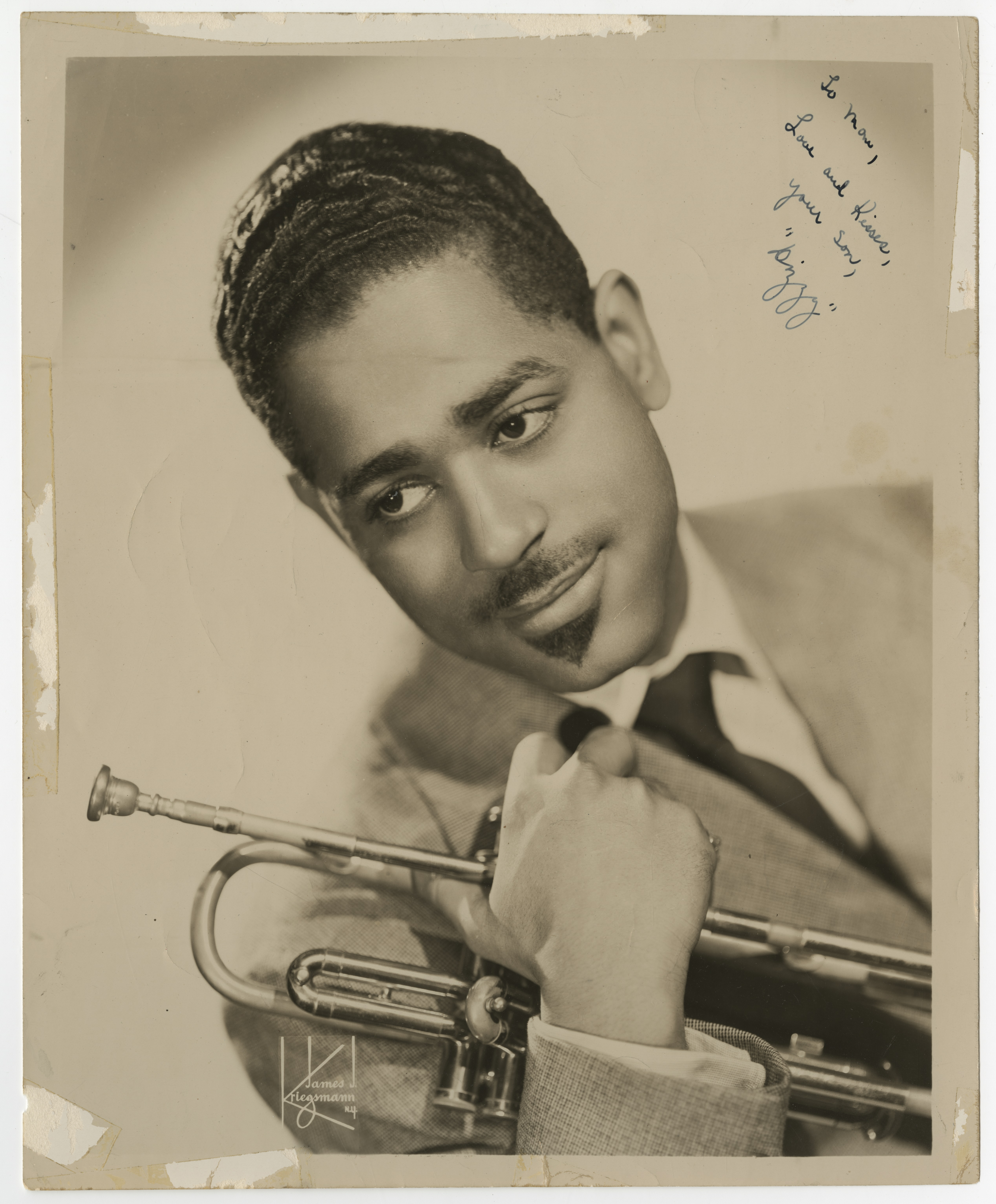 A sepia toned headshot of a young Dizzy Gillespie posing with his trumpet. He wears a suit and tie and has a tidy mustache. The inscription reads
