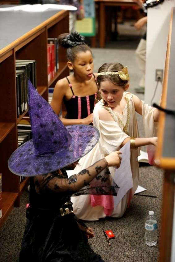 Three Blair Academy students look for answers to a scavenger hunt clue in music reference books during the Halloween Open House..