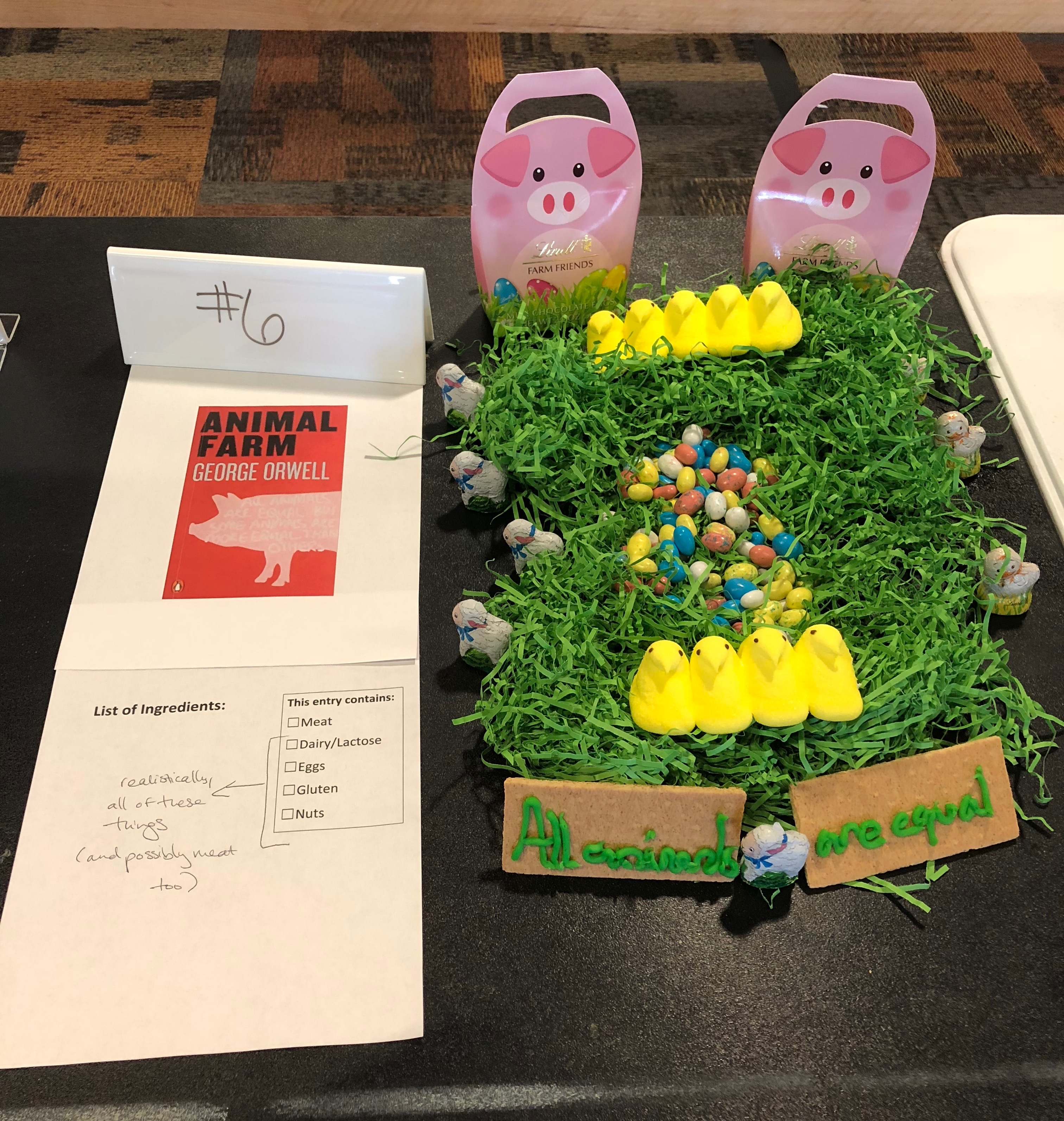 This tribute to George Orwell's Animal Farm includes a bed of grass adorned by peeps, jelly beans eggs, and chocolate pigs, lambs, and chickens. The pigs are several times larger than all the other animals.