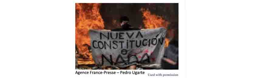 "Man in front of a fire and holding a sign that says ""Nueva Constitucion o Nada"""