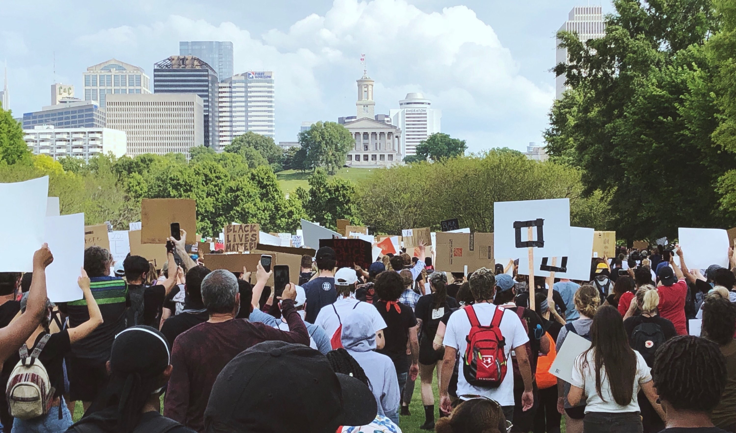 Hundreds of protesters hold signs and march up the Bicentennial Mall toward the Tennessee Capitol building