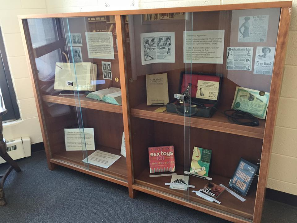 A wide shot of the exhibit of 19th century medical books, an antique vibrator, and modern books about sex toys