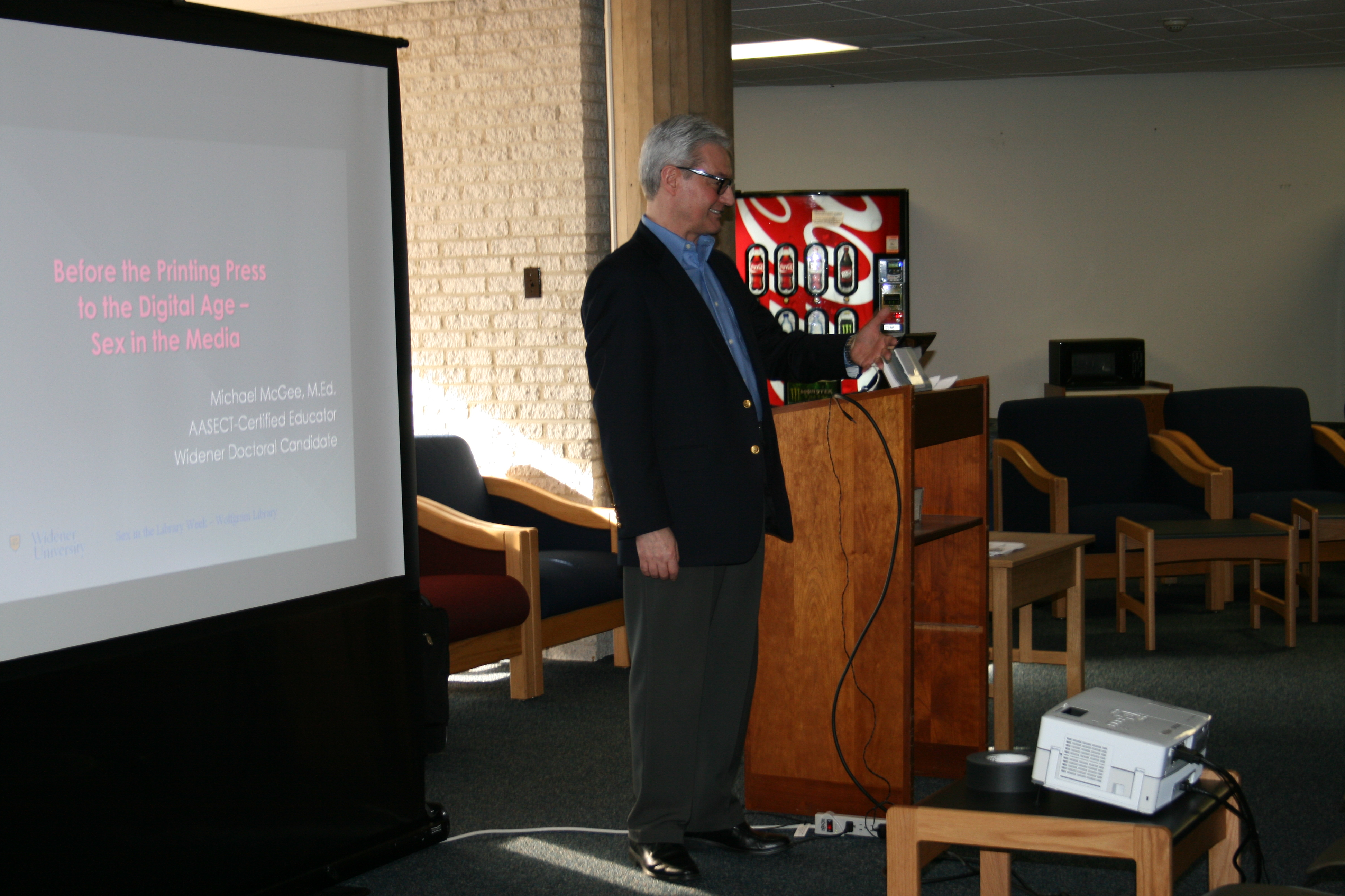 A white man in a suit standing next to a screen presenting information on sex in the media