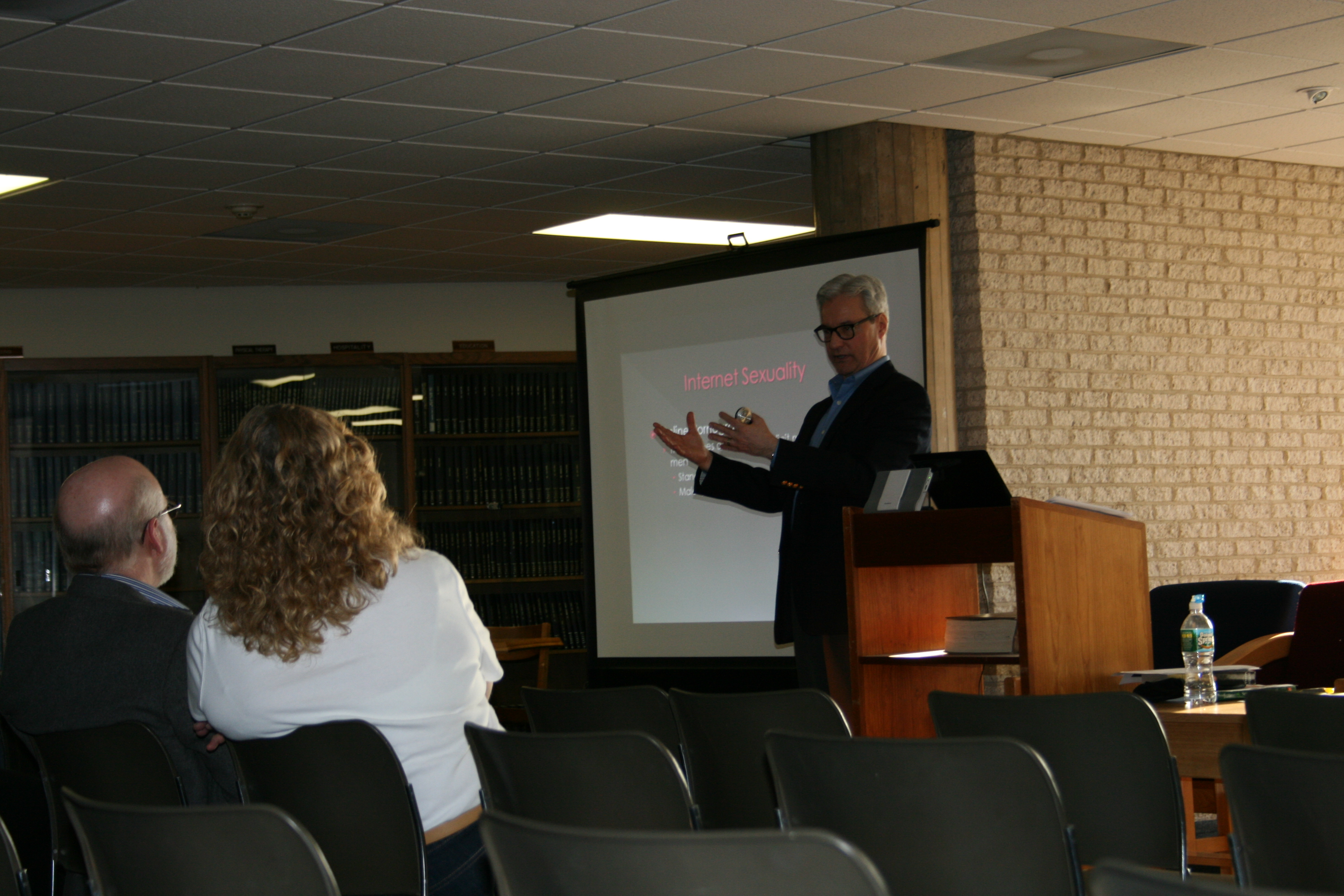 A photo of a white man standing next to a screen presenting information on sex in the media