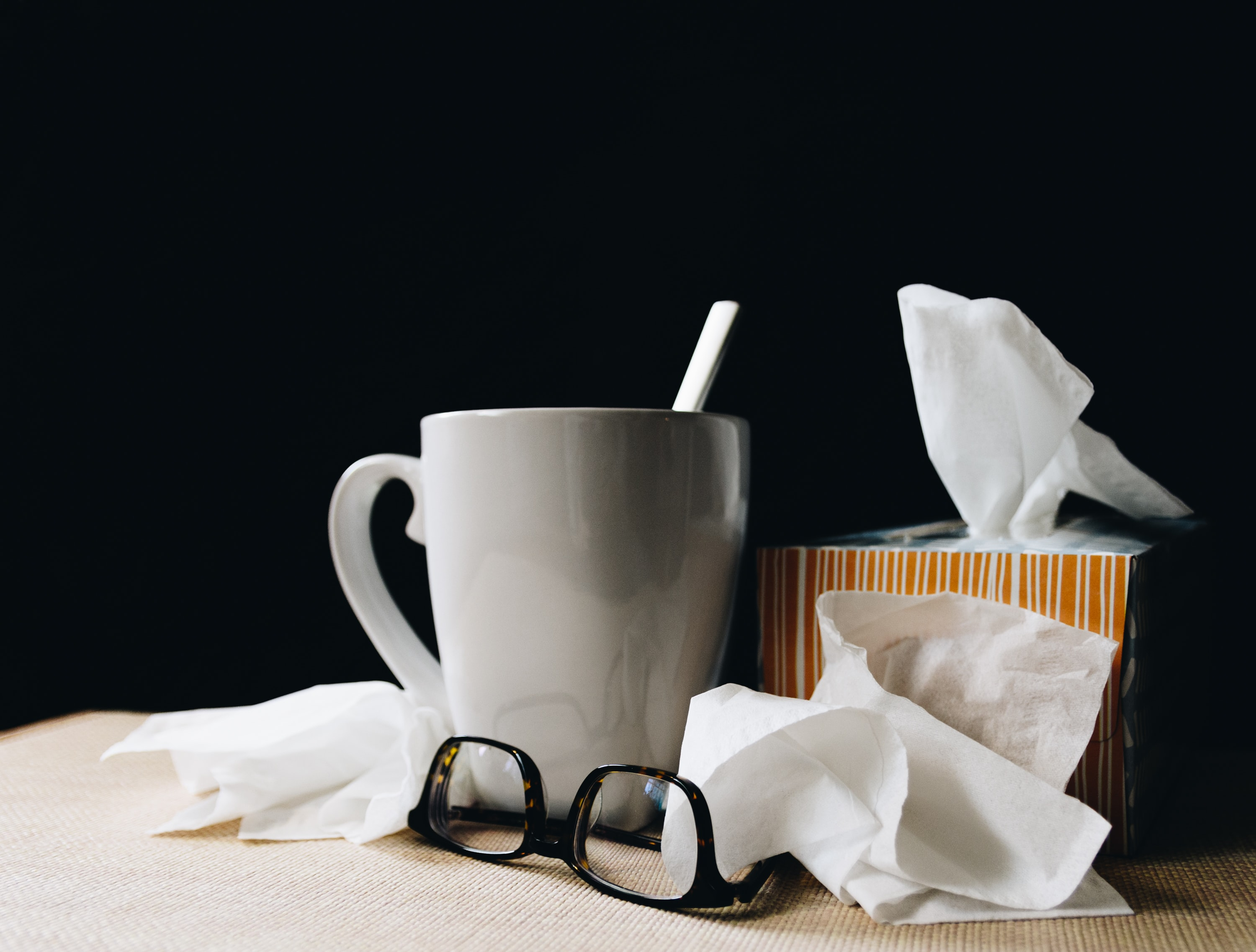 A photo of a mug and tissue box, surrounded by used tissues, on a table.