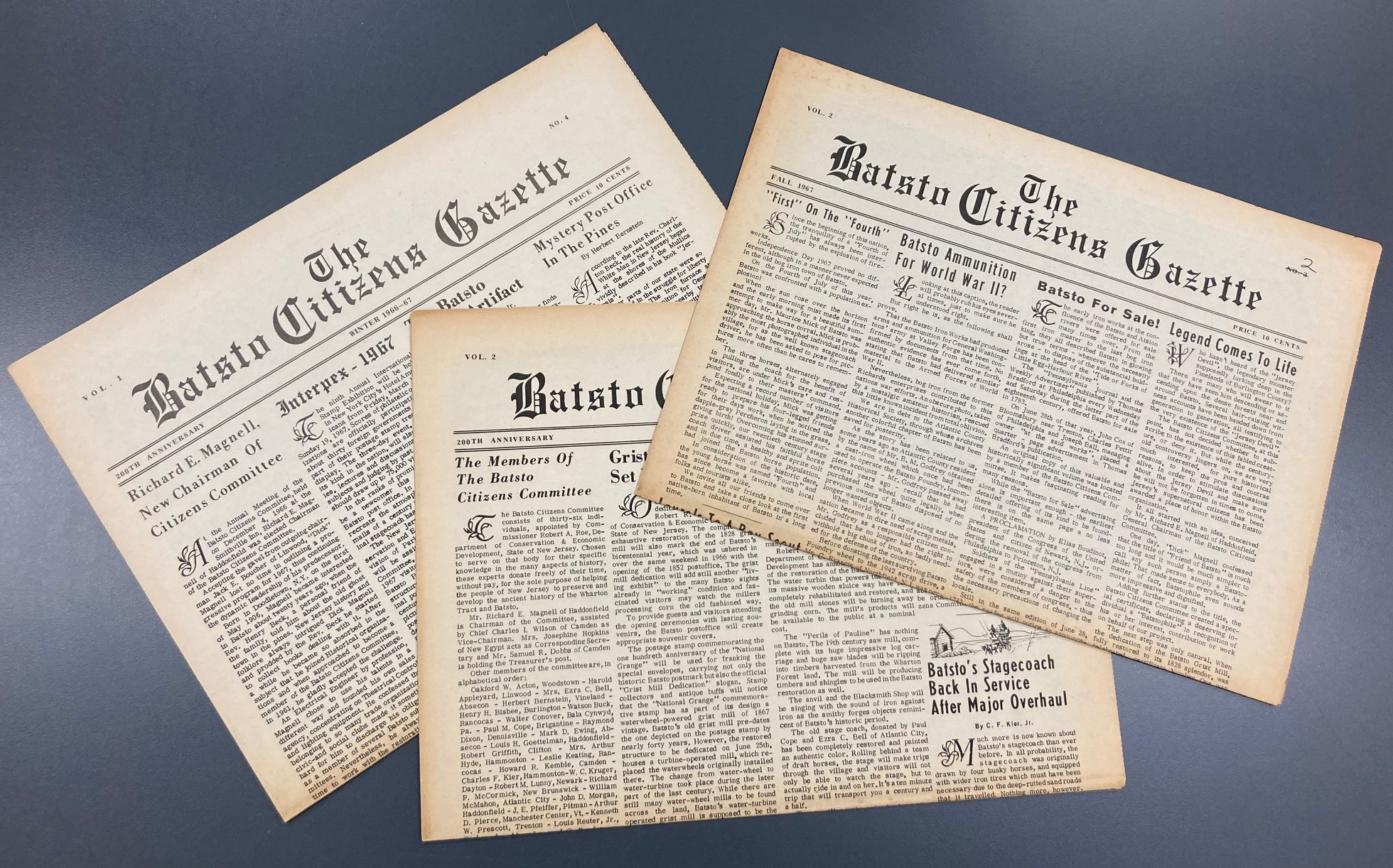 three copies of a newspaper on a gray background