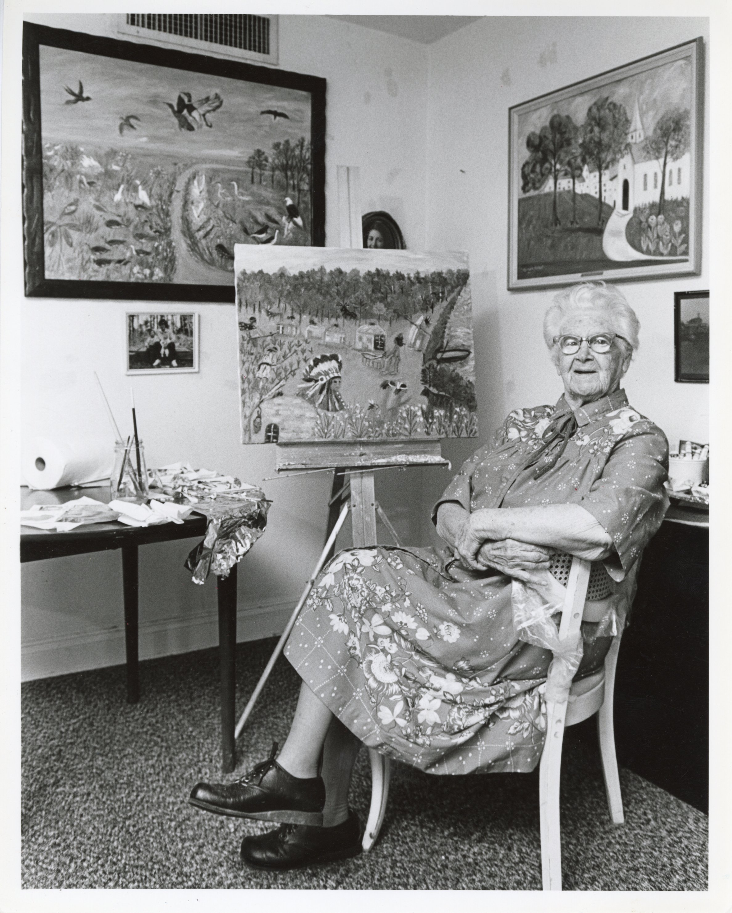 older woman sitting in a chair in front of several pieces of art depicting agricultural scenes