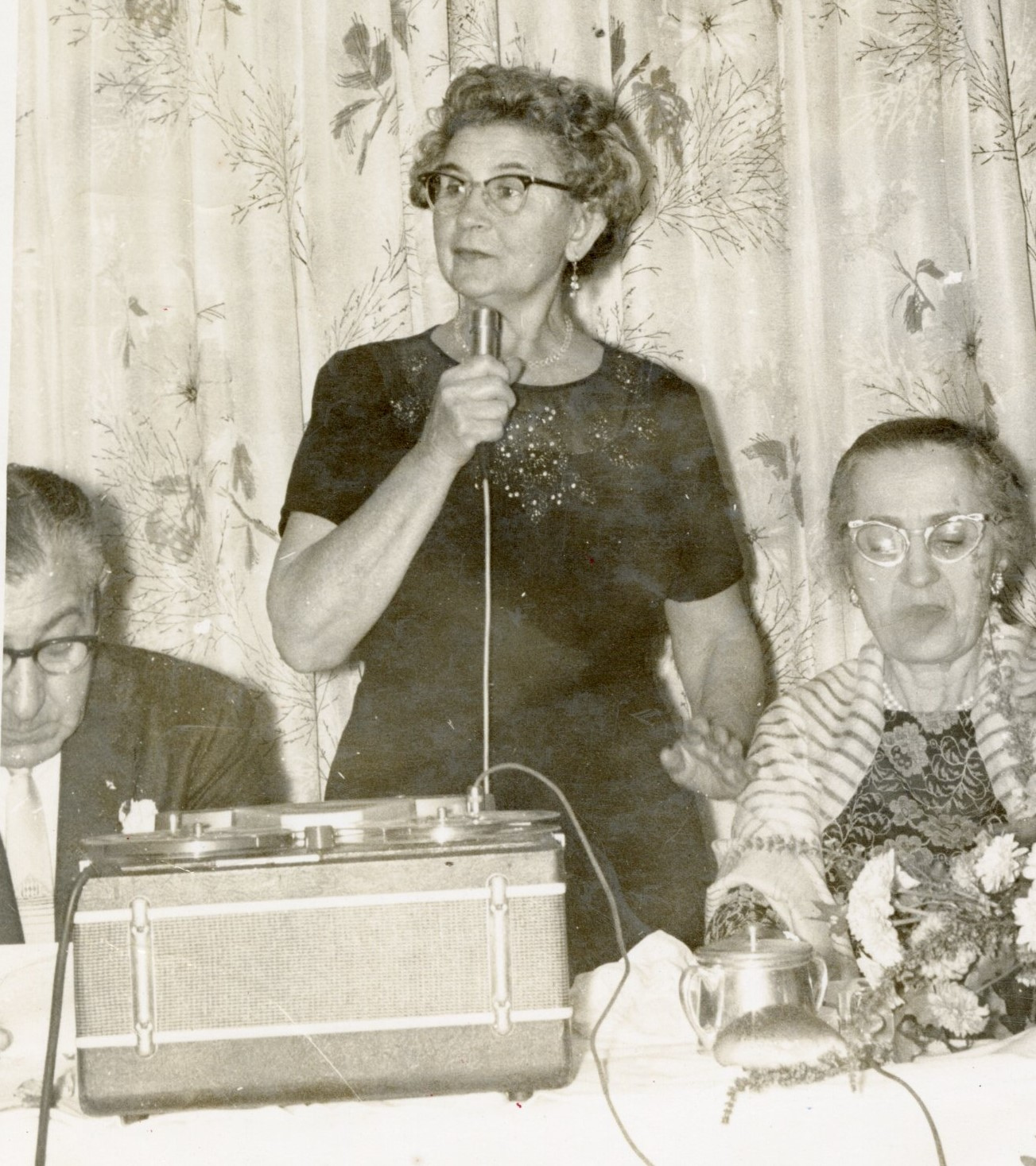 Photograph of woman standing and speaking into a microphone