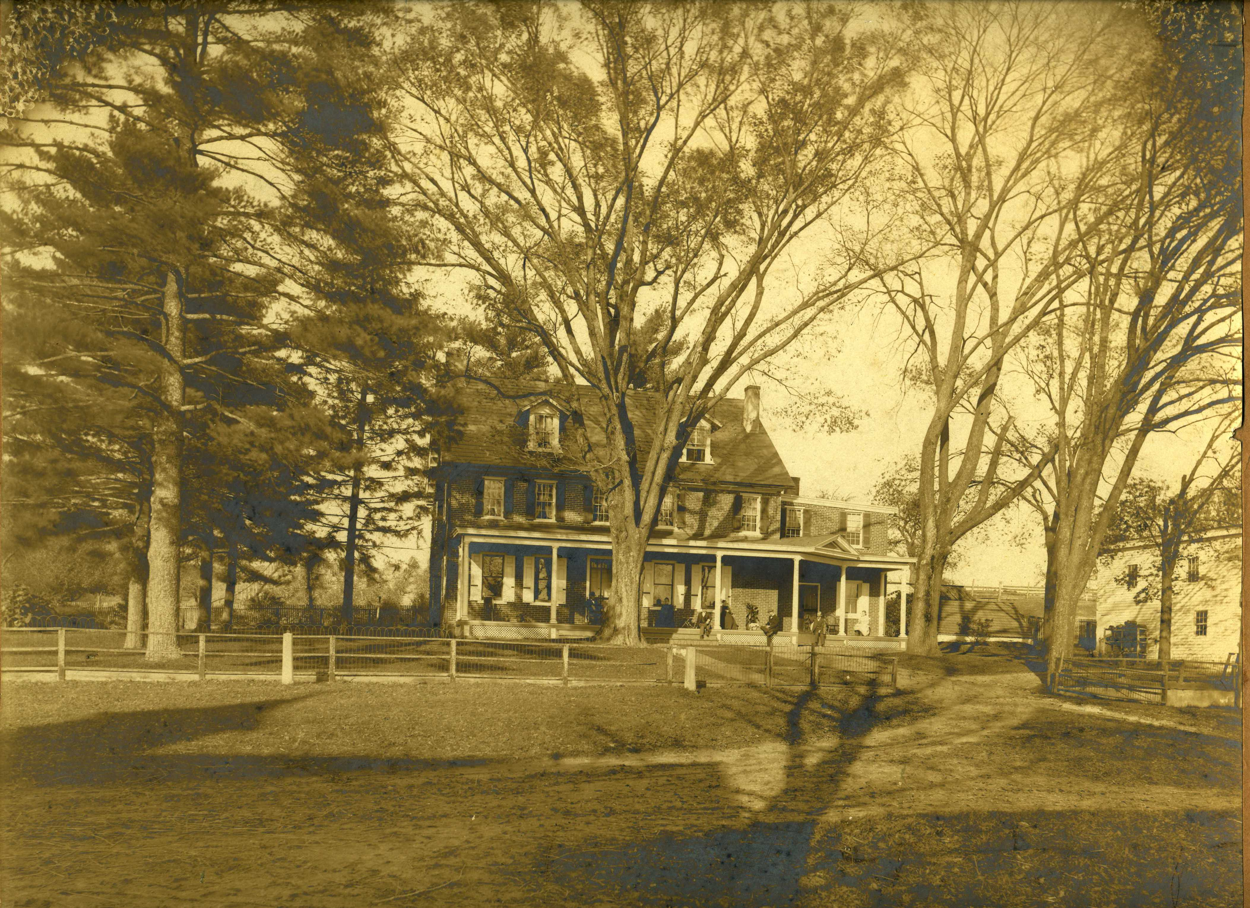 Photograph of building with trees in front. Building has large porch.