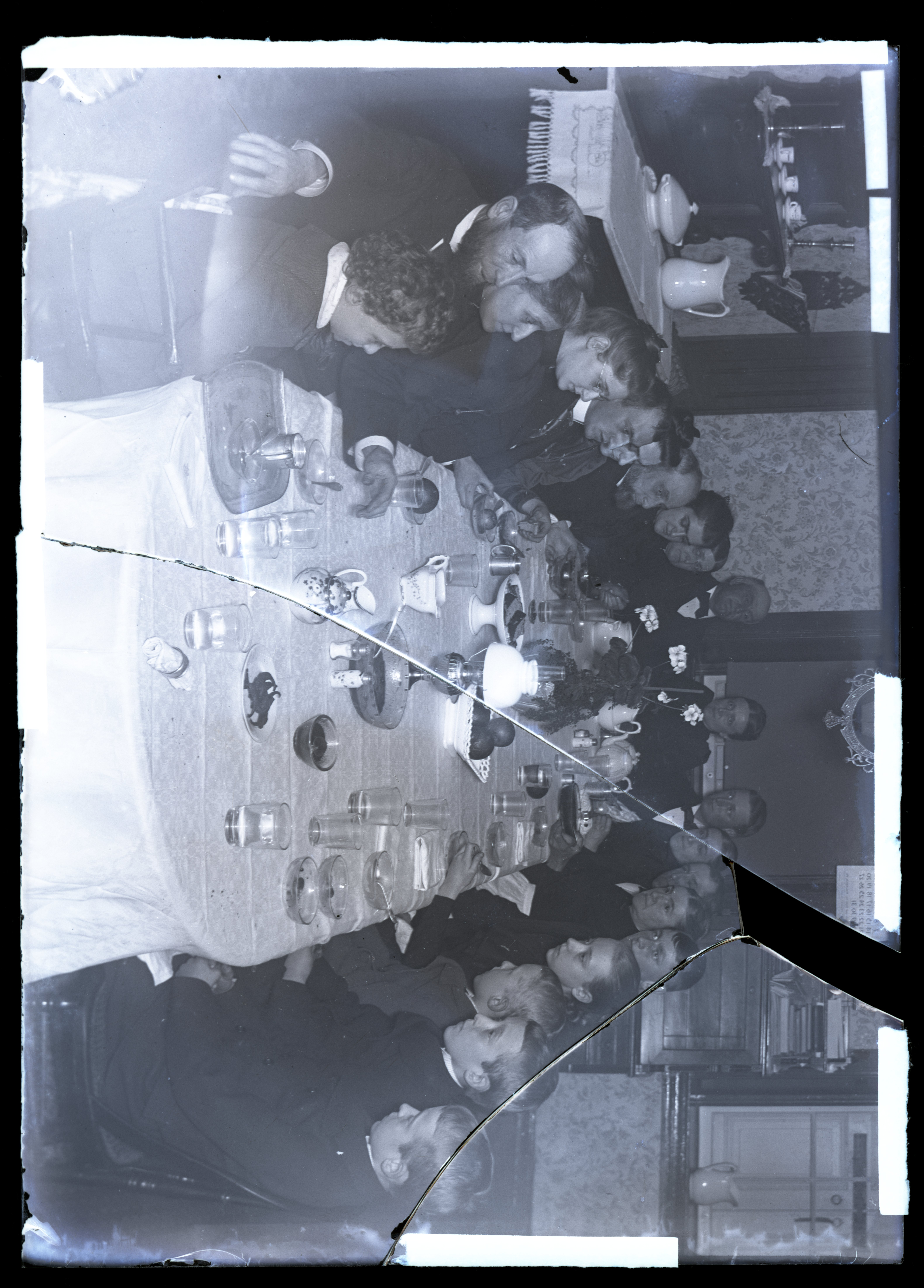 Photograph of large group of people, seated on either side of a long table set for a meal.