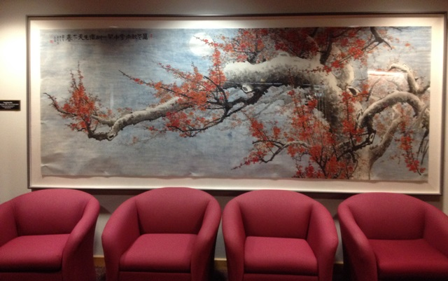 Large framed painting hanging on the wall of a tree with blossoms
