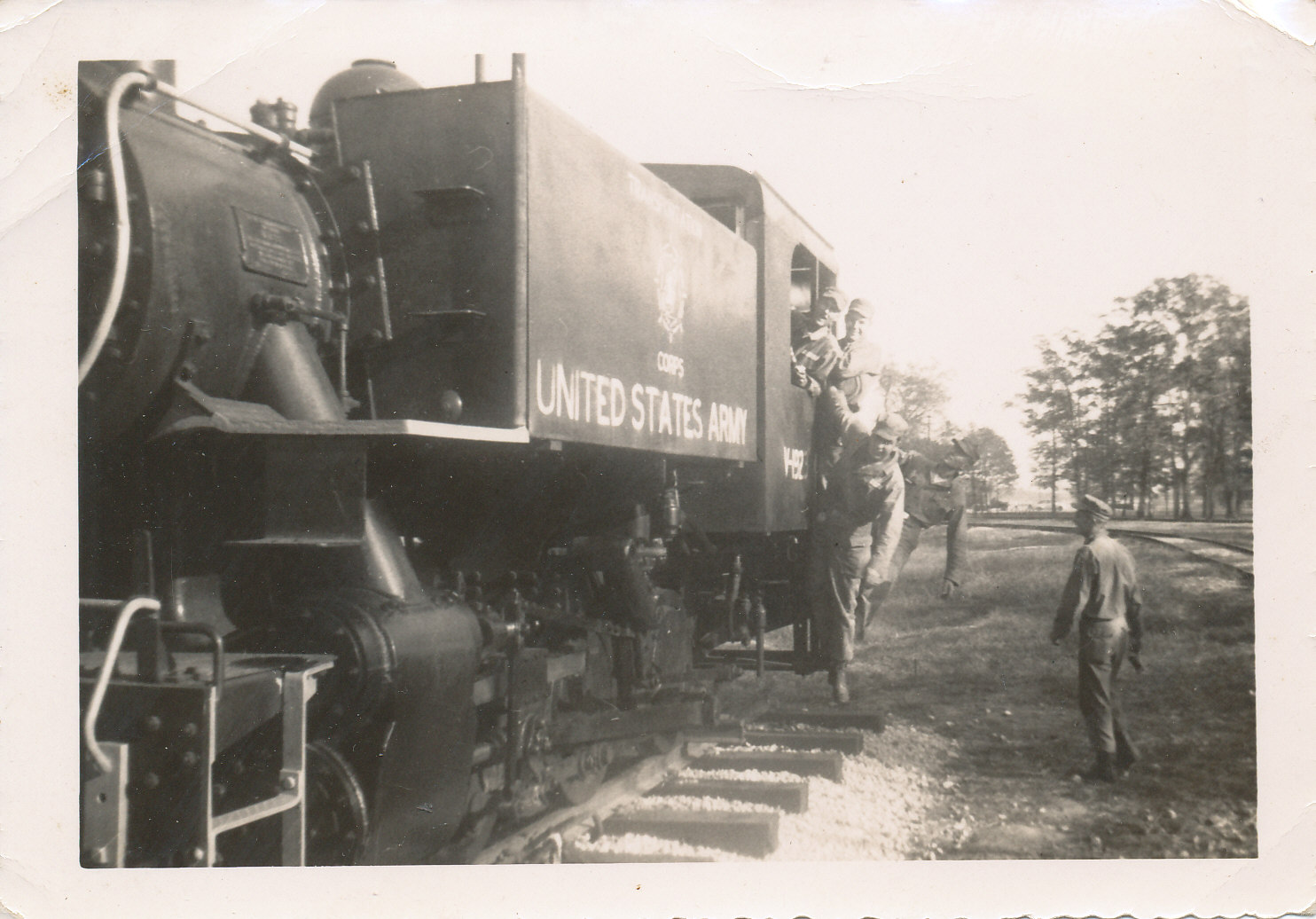 Black and white photo of man hanging from railroad car