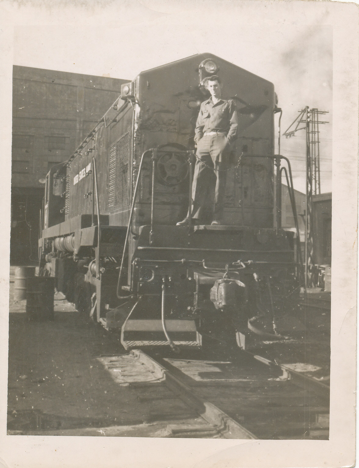 Black and white photo of man standing on railroad car